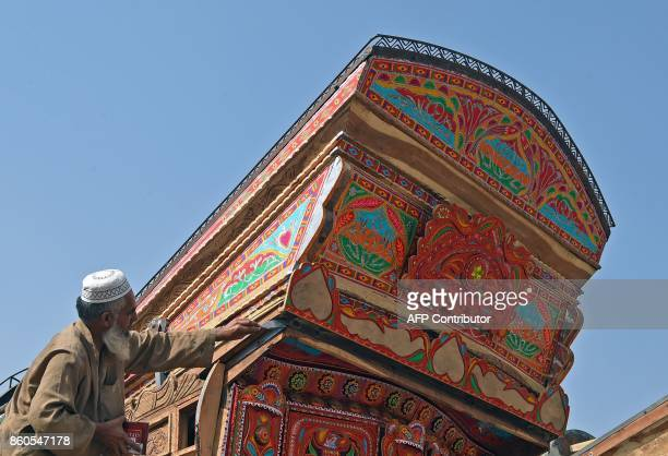 A Pakistani truck painter paints colourful decorations onto a goods truck at a workshop in Peshawar on October 12 2017 MAJEED