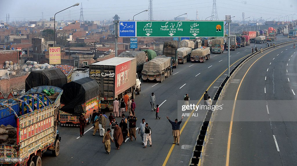 Pakistani trucks are seen parked on a bridge during a protest against the Quetta bombing, in Lahore on February 19, 2013. Thousands of Pakistani Shiite Muslims called off nationwide protests Tuesday and agreed to bury the dead from a bomb attack that killed 89 people, after the government promised to arrest those responsible. AFP PHOTO/Arif ALI