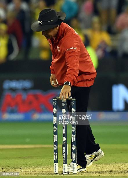 Pakistani umpire Aleem Dar removes the bails from the stumps after the Pool A 2015 Cricket World Cup match between Australia and England at the...