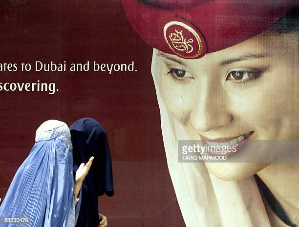 Pakistani veiled women walk in front of a billboard featuring an advertisement for an airline in Peshawar 13 July 2005 Islamic hardliners ruling...