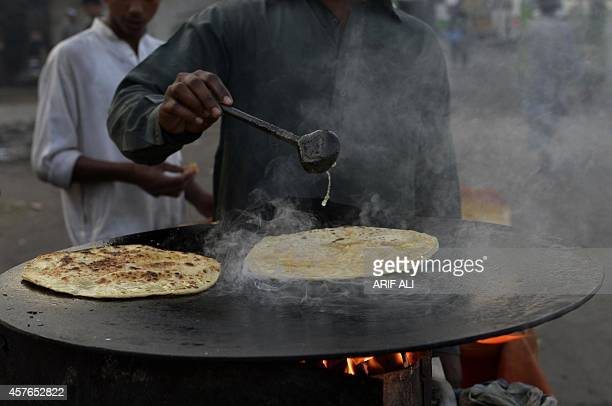 A Pakistani vendor fries aloo paratha at a temporary roadside stall in Lahore on October 22 2014 AFP PHOTO/ Arif ALI