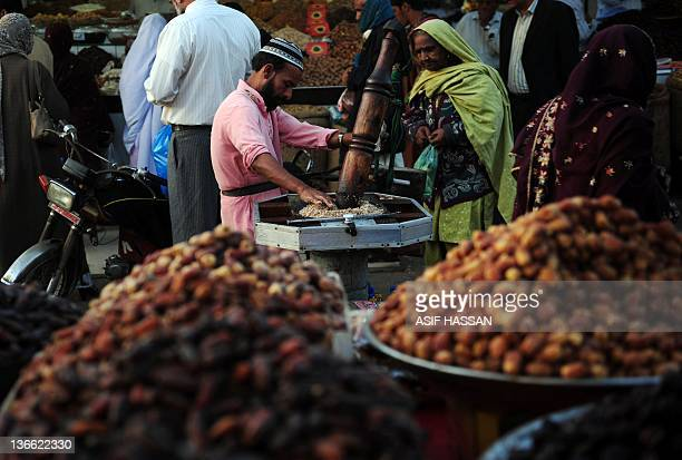 A Pakistani vendor Mohammad Ameer extrudes almond oil from a manual press at a market in Karachi on January 9 2012 The World Bank has said it would...
