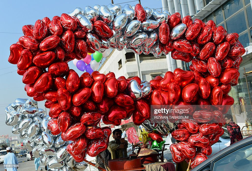A Pakistani vendor prepares heart-shaped balloons for sale ahead of Valentine's day in Karachi on February 13, 2013. Valentine's Day is increasingly popular among younger Pakistanis, many of whom have taken up the custom of giving cards, chocolates and gifts to their sweethearts to celebrate the occasion. AFP PHOTO/Rizwan TABASSUM