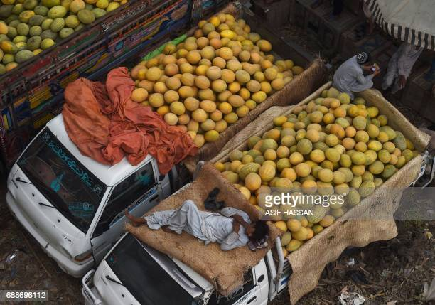 A Pakistani vendor rests on a truck loaded with cantaloupe at a fruit and vegetable market in Karachi on May 26 2017 Pakistan's economy expanded...