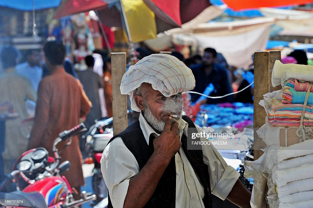 A Pakistani vendor smokes a cigarette at his stall in Rawalpindi on May 31, 2013, on World No Tobacco Day. Governments worldwide must ban all forms of tobacco marketing, not just billboards and TV ads, as companies find new ways to tap the market, the World Health Organization said May 29. AFP PHOTO/Farooq NAEEM