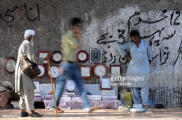 A Pakistani vendor waits for customers as he sells cheap clocks on a footpath in Saddar bazaar a neighbourhood of Karachi on March 15 2010 AFP PHOTO/...