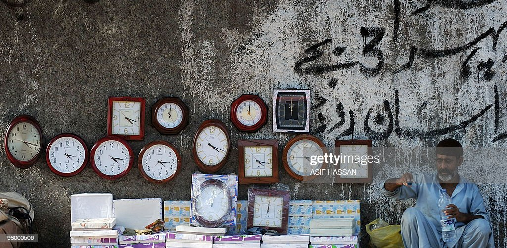 A Pakistani vendor waits for customers as he sells cheap clocks on a footpath in Saddar bazaar a neighbourhood of Karachi on March 15 2010 AFP PHOTO/...