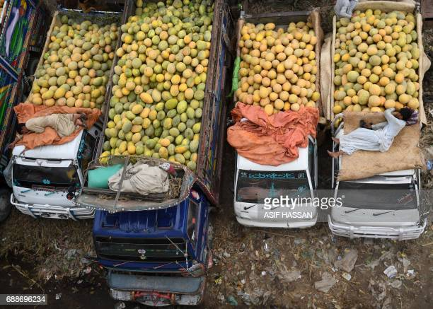 Pakistani vendors rest on their trucks loaded with cantaloupe at a fruit and vegetable market in Karachi on May 26 2017 Pakistan's economy expanded...