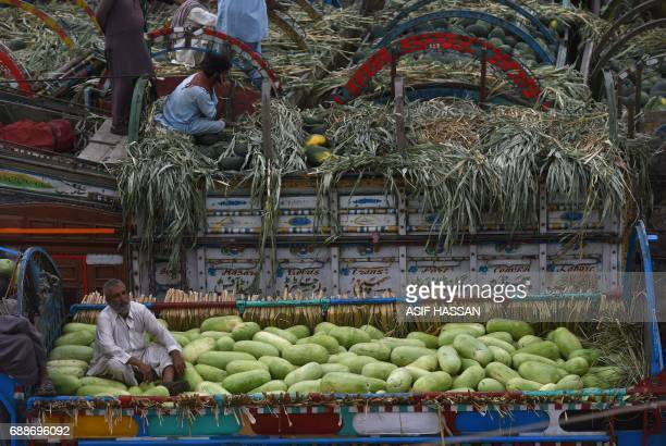 Pakistani vendors sit on watermelons on their trucks while they wait for customers at a main fruit and vegetable market in Karachi on May 26 2017...