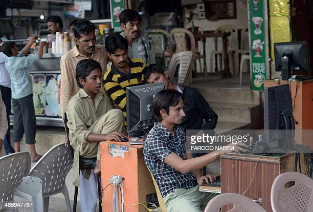 Pakistani vendors use computers to upload music and video files onto their client's mobile phones at a market in Faisalabad on May 9 2014 Pakistan is...