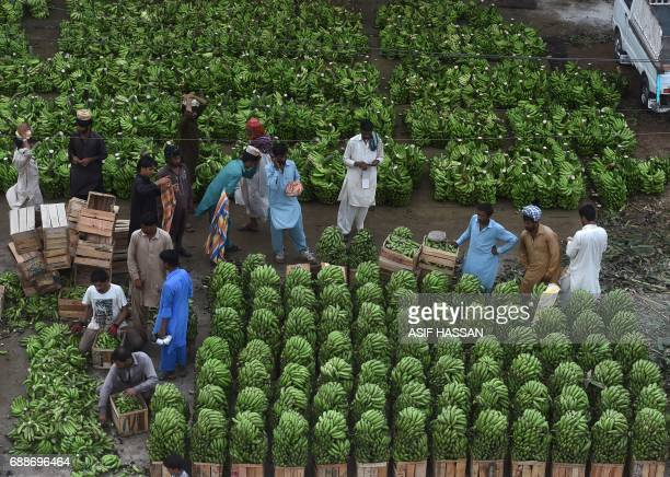 Pakistani vendors wait for customers at a fruit and vegetable market in Karachi on May 26 2017 Pakistan's economy expanded almost 53 percent in the...