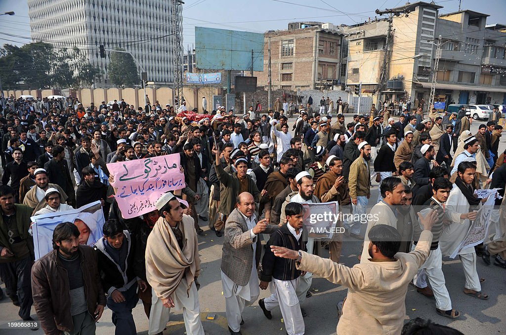 Pakistani villagers from the northwest carry placards during a protest in the provincial capital Peshawar on January 16, 2013. Demonstrators said gunmen wearing military uniforms stormed homes in Bara Tehsil in Khyber Agency, some 30 kilometers from Peshawar and shot 18 villagers dead in an overnight raid.