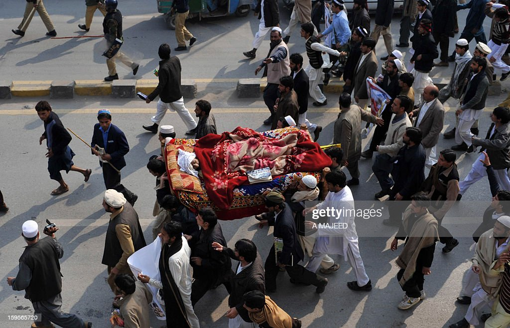 Pakistani villagers from the northwest carry the body of their relative during a protest in provincial capital Peshawar on January 16, 2013. Demonstrators said gunmen wearing military uniforms stormed homes in Bara Tehsil in Khyber Agency, some 30 kilometers from Peshawar and shot 18 villagers dead in an overnight raid. AFP AFP PHOTO/A MAJEED