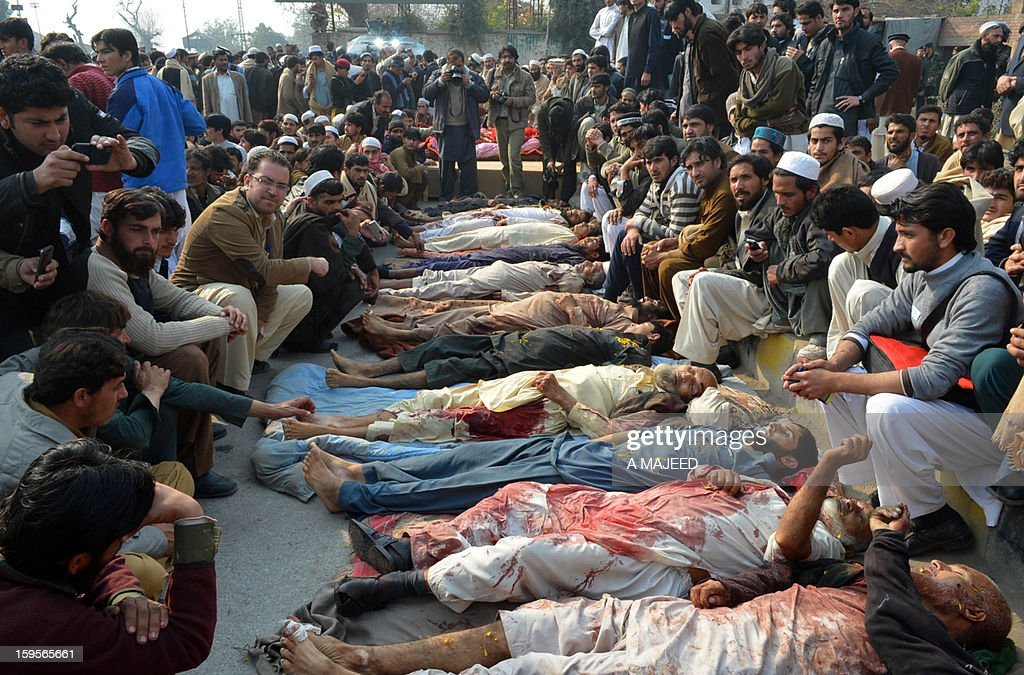 Pakistani villagers from the northwest gather around the dead bodies of their relatives during a protest in provincial capital Peshawar on January 16, 2013. Demonstrators said gunmen wearing military uniforms stormed homes in Bara Tehsil in Khyber Agency, some 30 kilometers from Peshawar and shot 18 villagers dead in an overnight raid.
