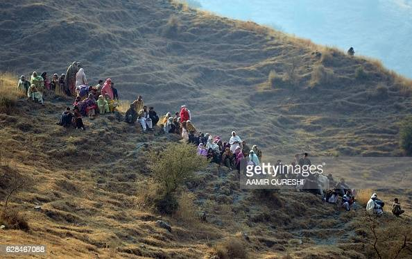 Pakistani villagers gather near a plane crash site in the village of Saddha Batolni in the Abbottabad district of Khyber Pakhtunkhwa province on...
