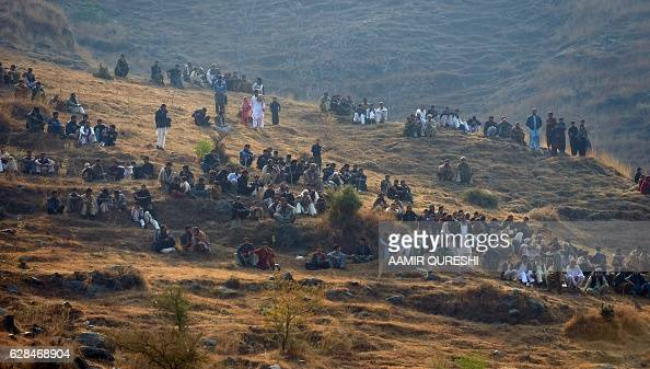 Pakistani villagers gather near the site of a Pakistani plane crash near the village of Saddha Batolni in the Abbottabad district of Khyber...