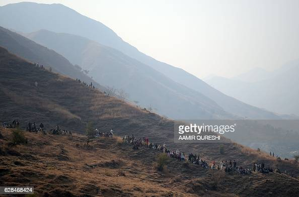 Pakistani villagers gather near the site of a plane crash in the village of Saddha Batolni in the Abbottabad district of Khyber Pakhtunkhwa province...