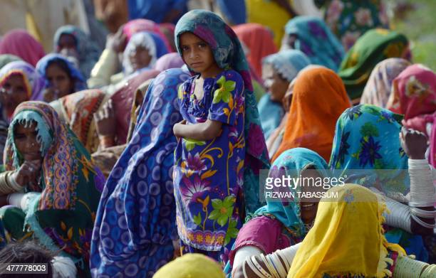 Pakistani villagers wait to receive relief supplies outside a military camp in Mithi the capital of Tharparkar district some 300 kilometres from...