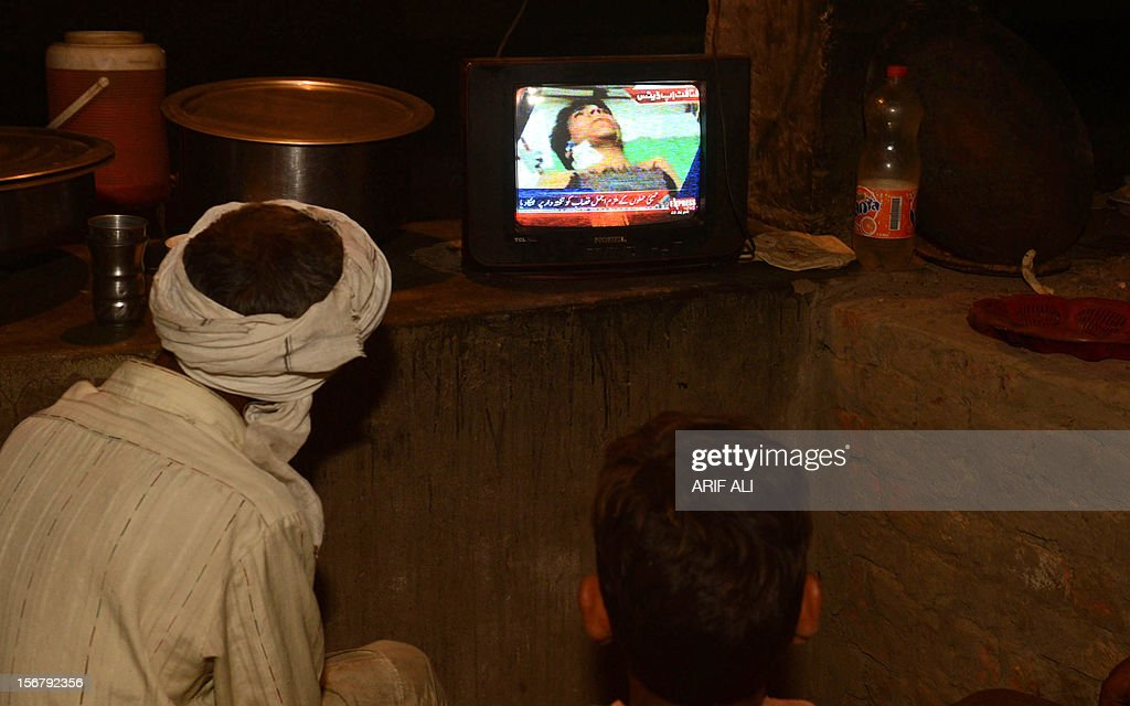 Pakistani villagers watch the news on television of Ajmal Kasab who was hanged in an Indian prison at Kasab's village in Farid kot some 370...