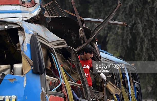 A Pakistani volunteer looks from a destroyed bus after a bomb blast in Peshawar on March 16 2016 At least 16 people were killed and more than two...