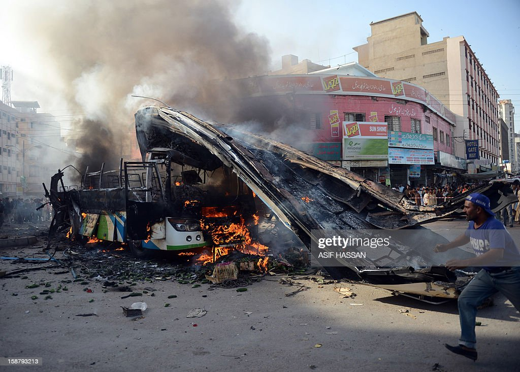 A Pakistani volunteer runs past a destroyed burning bus at the site of an explosion in Karachi on December 29, 2012. At least four people were killed and dozen wounded when a loud explosion ripped apart a passenger bus outside the railway station in the port city of Karachi, the nature of the explosion could not be ascertained. AFP PHOTO/Asif HASSAN