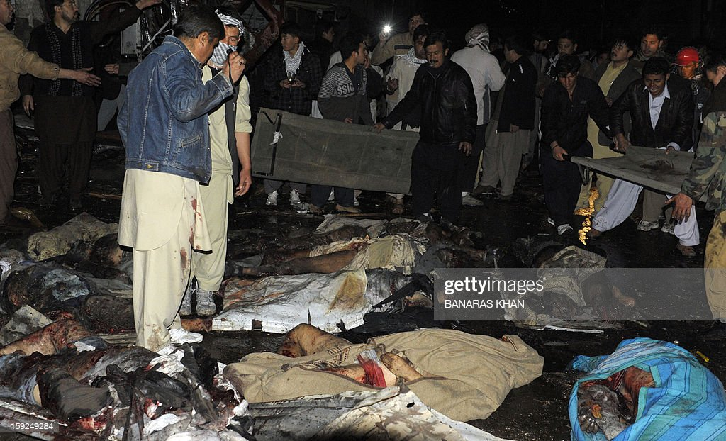 Pakistani volunteers and local residents remove dead bodies from the site of a bomb attack in Quetta on January 10, 2013. At least 57 people were killed in the southwestern city of Quetta as two successive bombs exploded, with one bomb blast occurring outside a snooker club hours after another blast had already left many casualties, police said. AFP PHOTO / BANARAS KHAN