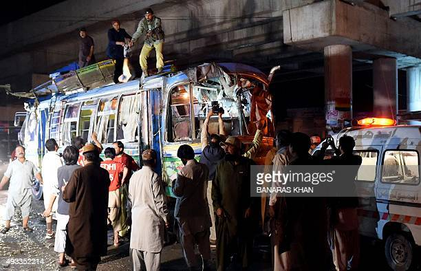 Pakistani volunteers and residents gather beside a damaged bus after a bomb explosion in Quetta on October 19 2015 At least 10 people were killed and...
