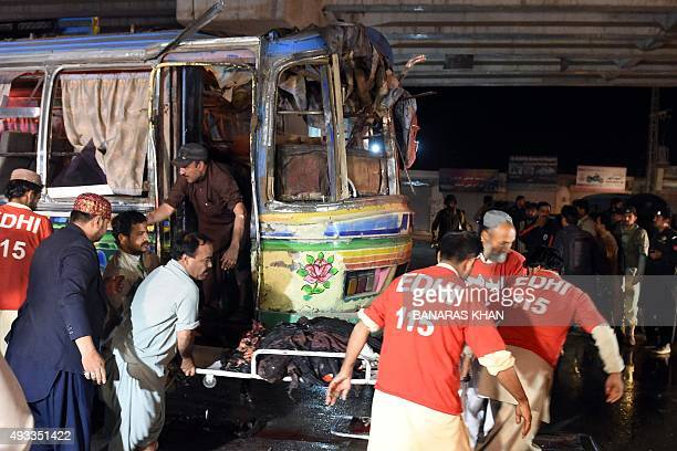 Pakistani volunteers and residents move the body of a blast victim from a bus after a bomb explosion in Quetta on October 19 2015 At least 10 people...