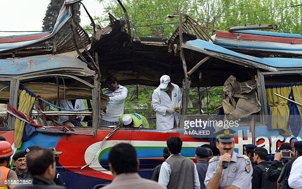 Pakistani volunteers and security forces inspect a destroyed bus after a bomb blast in Peshawar on March 16 2016 At least 16 people were killed and...