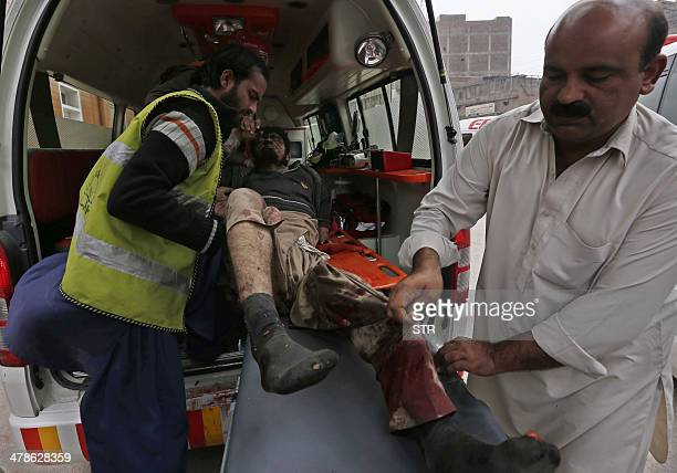 Pakistani volunteers carry an injured blast victim to a hospital after a suicide attack in Peshawar on March 14 2014 A suicide bomb attack targeting...