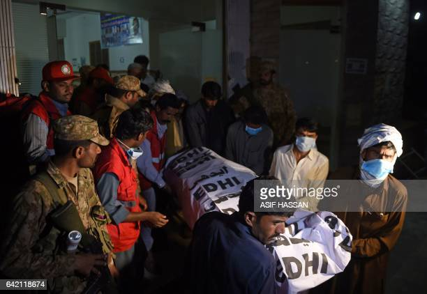 Pakistani volunteers carry the body of a victim from a hospital in the town of Sehwan a day after a bomb attack hit the 13th century Muslim Sufi...