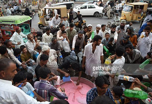 Pakistani volunteers distribute drink to people before breaking their fast during the Muslim fasting month of Ramadan in Karachi on June 20 2015...
