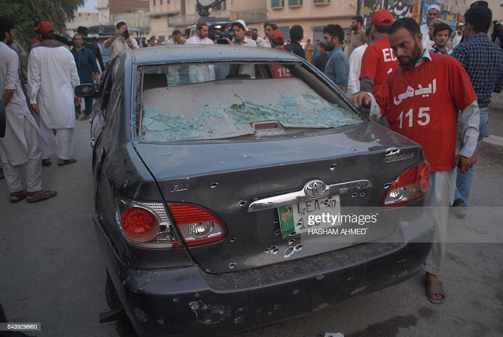 Pakistani volunteers gather beside a damaged vehicle at the site of a roadside bomb explosion in Peshawar on June 30, 2016. Two policeman were killed and six civilians were wounded in two separate attacks on June 30 in Pakistan's restive northwest Khyber Pakhtunkhawa province, officials said. / AFP / HASHAM