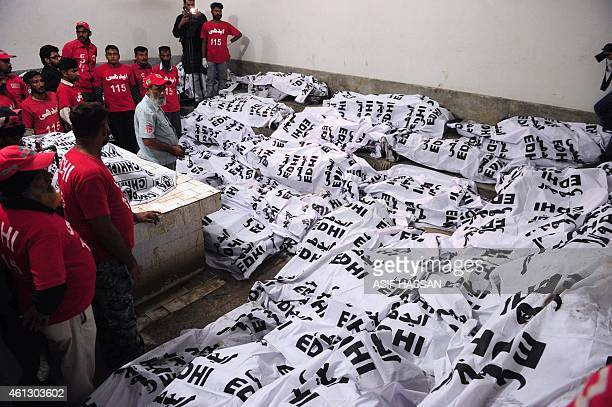 Pakistani volunteers gather beside the bodies of victims at a hospital in Karachi early on January 11 following an accident between a passenger bus...