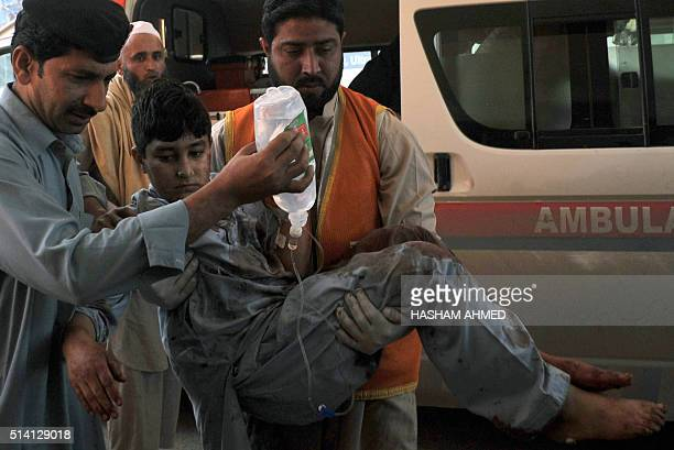 TOPSHOT Pakistani volunteers move a victim injured in a suicide bombing to a hospital in Peshawar on March 7 after an attack on a court complex in...