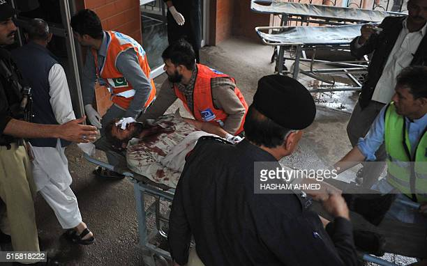 Pakistani volunteers move an injured blast victim to hospital after a bomb blast in a bus in Peshawar on March 16 2016 A blast ripped through a bus...