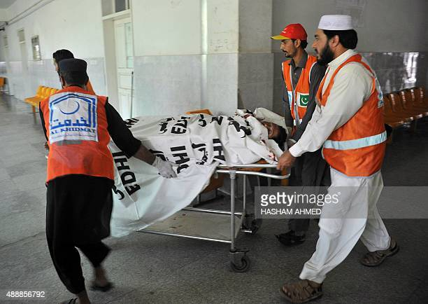 Pakistani volunteers move the body of a victim who was kiiled in an attack by militants on a Pakistan Air Force base in Peshawar on September 18 2015...