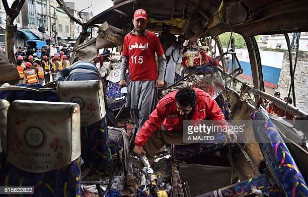 Pakistani volunteers search a destroyed bus after a bomb blast in Peshawar on March 16 2016 At least 16 people were killed and more than two dozen...