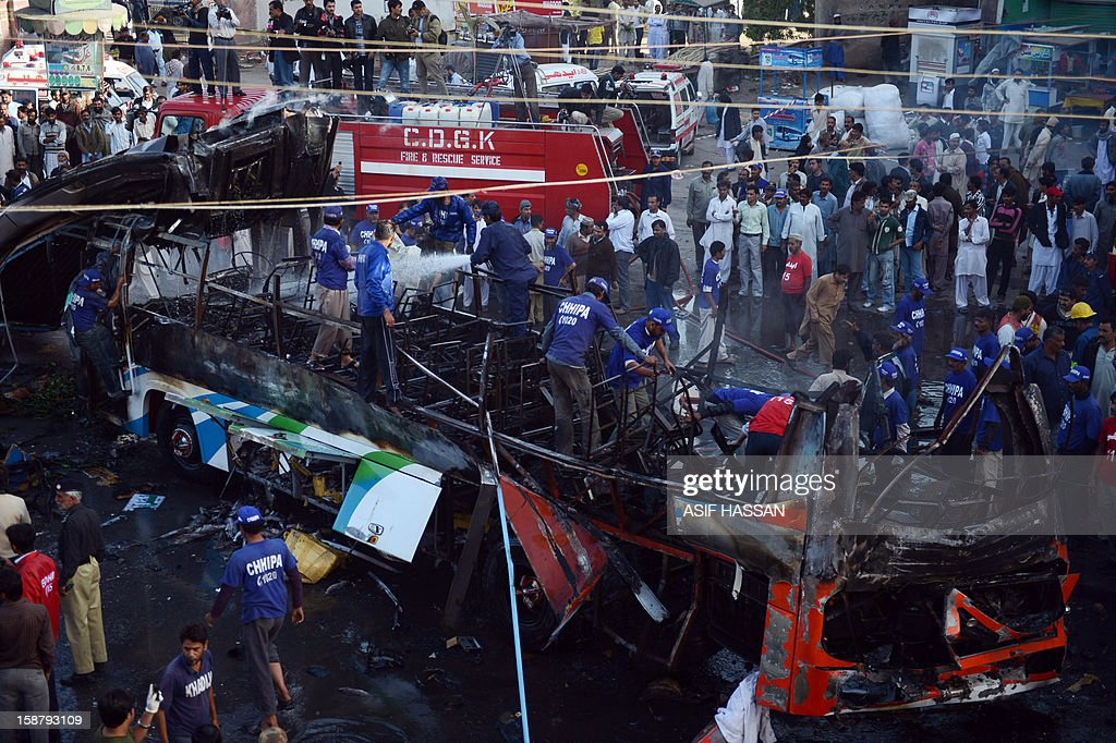 Pakistani volunteers search for victims in a destroyed passenger bus after an explosion in Karachi on December 29, 2012. At least four people were killed and dozen wounded when a loud explosion ripped apart a passenger bus outside the railway station in the port city of Karachi, the nature of the explosion could not be ascertained. AFP PHOTO/ Asif HASSAN