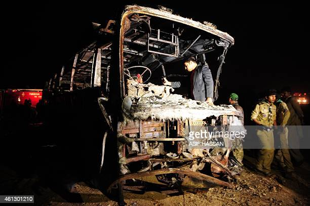 Pakistani volunteers search for victims inside a burnt out passenger bus after it collided with an oil tanker along the Super Highway near Karachi...