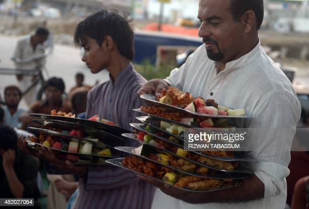 Pakistani volunteers serve Iftar food to devotees to break their past during the holy fasting month of Ramadan on a street in Karachi on July 11 2014...