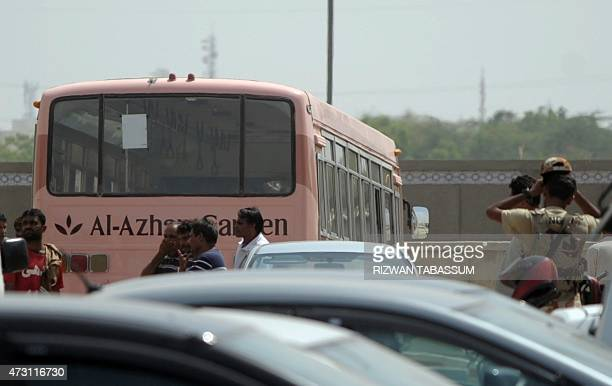 Pakistani volunteers stand beside the bus that was carrying Shiite Muslims and taken to a hospital after an attack by gunmen in Karachi on May 13...