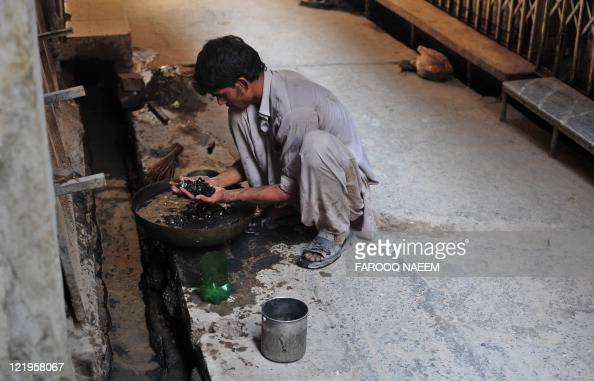 Pakistani Waqas scavenges for gold in drainage's at the gold market in Rawalpindi on August 19 2011 The price of gold hit a record high above $1863...