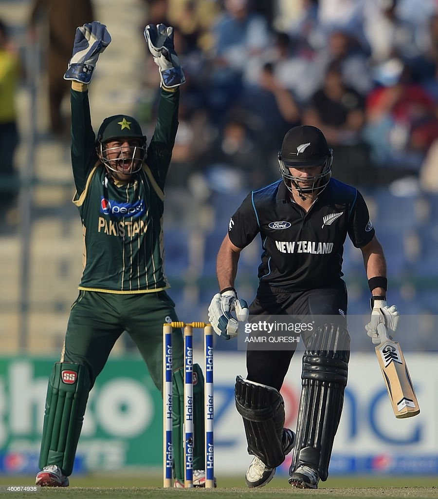 Pakistani wicketkeeper Sarfraz Ahmed (L) lauds a successful leg before wicket appeal against New Zealand batsman Dean Brownlie during the fifth and final day-night international match between Pakistan and New Zealand at the Zayed International Cricket Stadium in Abu Dhabi on December 19, 2014. New Zealand captain Kane Williamson won the toss and opted to bat in the fifth and final day-night international against Pakistan in Abu Dhabi. AFP PHOTO/ Aamir QURESHI
