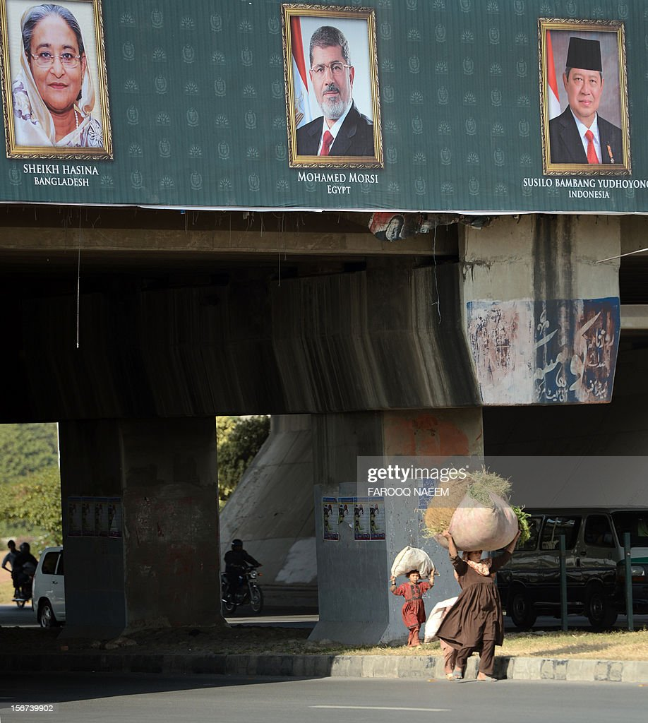 A Pakistani woman and her child carry bundles of grass over their heads as they walk under a billboard bearing the portraits of Bangladesh President Sheikh Hasina Wajid (L), Egyptian President Mohamed Morsi (C) and Indonesian President Susilo Bambang Yudhoyono ahead of the D8 summit in Islamabad on November 20, 2012. The biannual summit, established in 1997, will focus on economic challenges, development and peace in the region and among member countries. AFP PHOTO/Farooq NAEEM