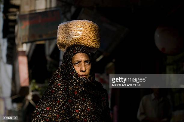 A Pakistani woman carries a bag of crisps as she walk in a street at sunset in Rawalpindi on the outskirts of the capital Islamabad on October 22...