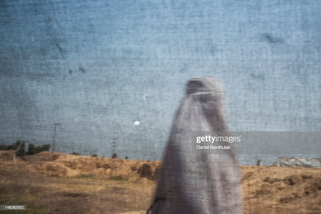 A Pakistani woman, displaced from their homes due to the Pakistan Army's latest military offensive in the Bara area of the Khyber Tribal Region in Northwest Pakistan, is seen through a screen as she walks though the Jalozai UNHCR Camp for Internally Displaced Person's (IDP's) on July 13, 2012 in Jalozai, Pakistan. Since January of this year, thousands of IDP's from the Bara area in Khyber Tribal Region have been forced to flee their homes due to the latest offensive by the Pakistan Military against militants in the area.The remote Tribal regions of Pakistan have been off-limits for Polio outreach vaccination teams due to security risks from militants. 'It has been a window of opportunity for us to be able to vaccinate people from the Tribal regions during this last influx (of IDP's) from Bara.' said Dr Imran from the Merlin Clinic at the Jalozai Camp.
