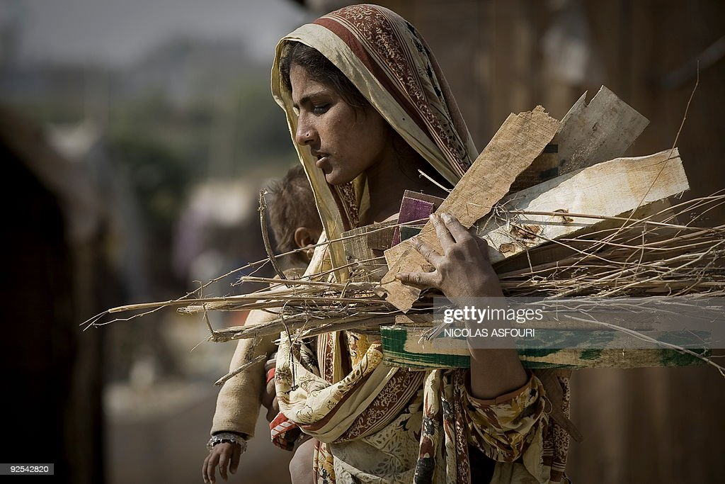 A Pakistani woman holds a baby and firewood as she walk in a slum in Rawalpindi on the outskirts of capital Islamabad on October 25 2009 The...