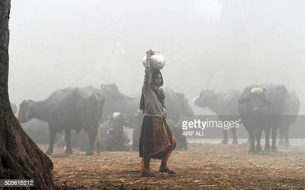 Pakistani woman holds a water pot during a cold and foggy morning in Lahore on January 19 2016 Ongoing foggy weather in Punjab and other parts of the...