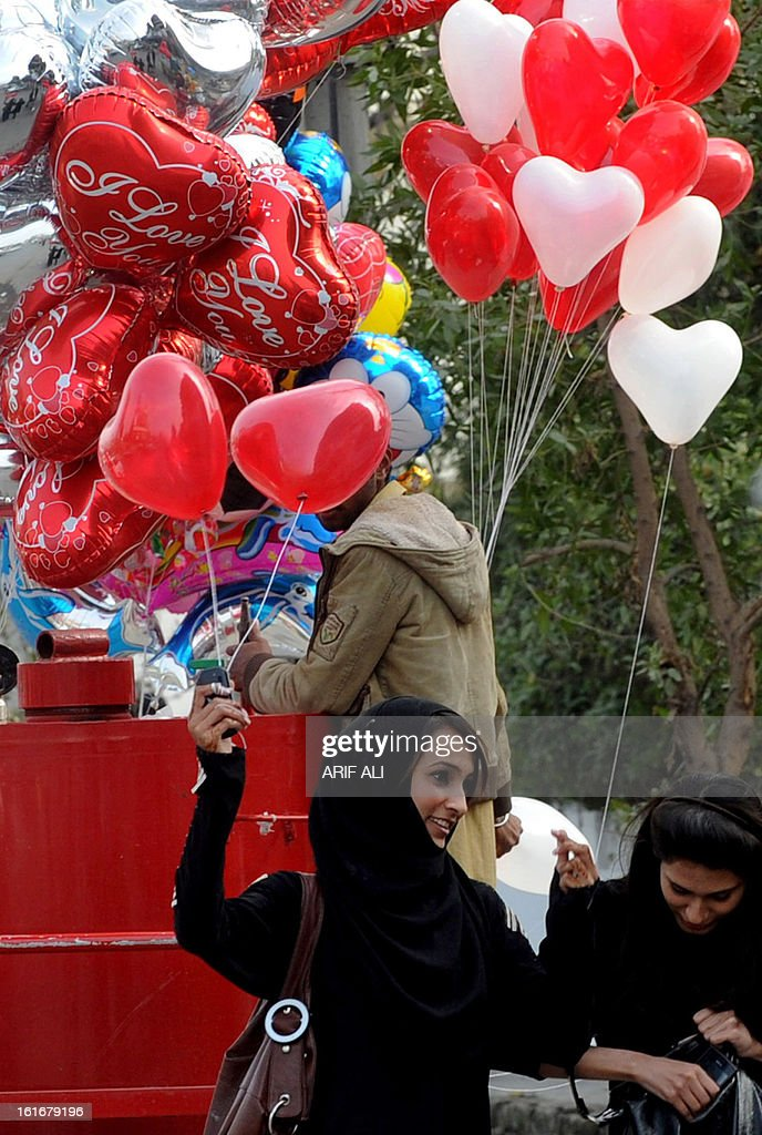 A Pakistani woman holds heart shaped balloons she purchased from a road-side vendor on Valentine's Day in Lahore on February 14, 2013. Pakistan's media regulator Wednesday asked television and radio stations to avoid offending religious sentiments and corrupting the nation's youth in their Valentine's Day broadcasts. AFP PHOTO/Arif ALI